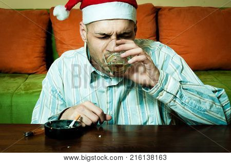 Young man with Santa Claus hat drink alcohol and smoking cigarette caused by New Year or Christmas hollidays depression and loneliness