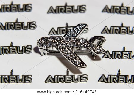 BERLIN - NOVEMBER 20 2017: Women's brooch in the form of an airplane on a background of small lapel pins AIRBUS.