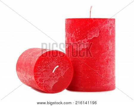 Two different in size, red wax candles with a wick on an isolated white background, candles next to each other, one lies with a fitter to the camera, concept of holidays, new year