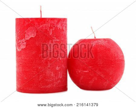 Two different in size and shape of red wax candles with a wick on an isolated white background, the candles stand next to each other, different in shape, one thick, the second in the shape of a ball