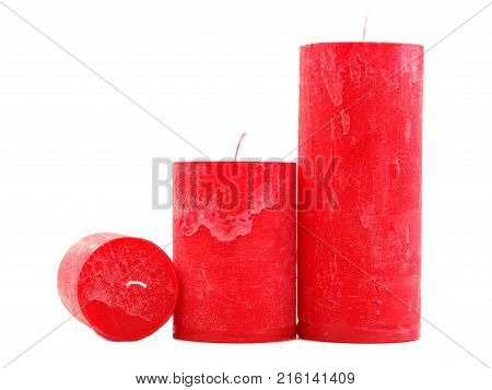 Three different sized red wax candles with a wick, isolated on a white background, two candles are standing, one is a fitter to the camera, different in height, concept of holidays, new year