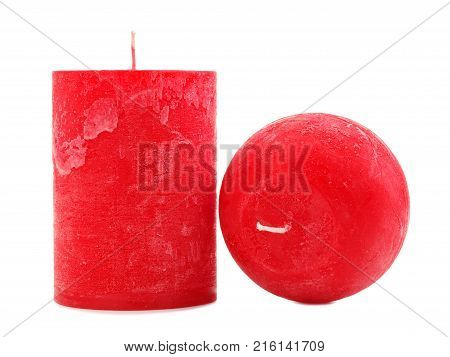 Two different in size and shape of red wax candles with a wick, on an isolated white background, a thick candle stands, the second in the form of a ball lies a phial to the camera