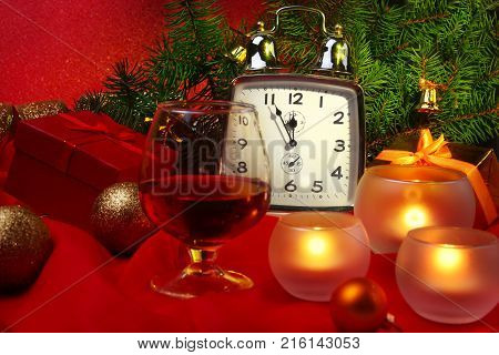Christmas clock, glass with cognac or whisky and candles. New Year's Decoration with gift boxes, christmas balls and tree. Celebration Concept for New Year