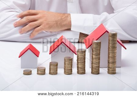 Midsection Of Businessperson With Different Size Houses And Stacks Of Coins On Table