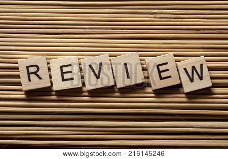 Word REVIEW written on wooden cubes. Wood abc.