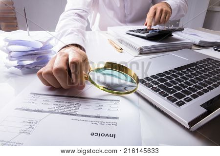 Midsection Of An Auditor Checking Invoice Using Magnifying Glass With Laptop And Documents On Desk