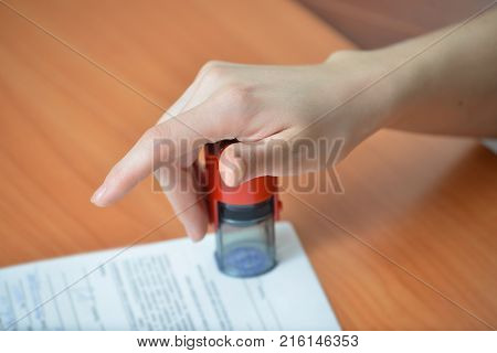 Female hand pushing rubber stamps on document at office table, closeup detail shoot