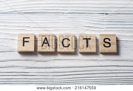 Word FACTS written on wooden cubes. Education concept.