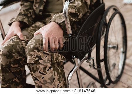 Veteran in wheelchair returned from army. Close-up photo veteran in a wheelchair. Wheelchairs and legs in military uniform.