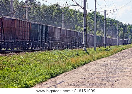 long freight train with freight cars goes by rail