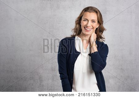 Cheerful mid adult woman laughing and looking at camera. Portrait of smiling businesswoman enjoying standing against grey wall. Happy mature woman looking at camera with toothy smile, copyspace.