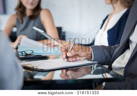 Closeup of hand of businessman holding pen and analyzing report during board meeting. Business people writing on document during annual meeting. Detail hand of business man fill the business contract.
