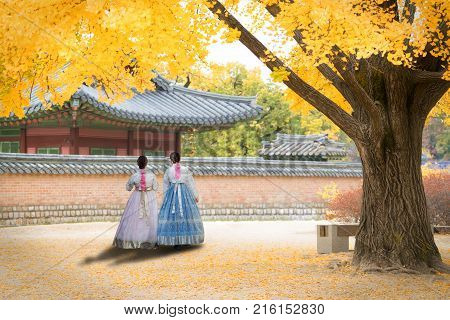 Asian Korean woman dressed Hanbok in traditional dress walking in Gyeongbokgung Palace in autumn season at Seoul South Korea.