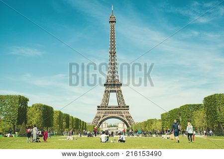 Paris France - May 62016 : Tourists chilling in park near Eiffel Tower Paris France. In year 2016 more than 15 million tourists visited the city of Paris.