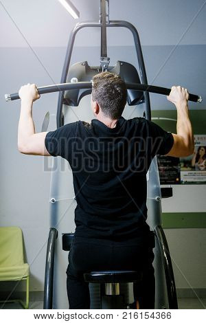 A man is engaged in a block simulator in a gym.  Work of personal trainer. Portrait Of Personal Trainer In Sports Outfit In Fitness Center Gym Standing Strong.