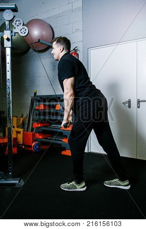 The guy is engaged in a crossover simulator. A man performs exercises in a gym.  Work of personal trainer. Portrait Of Personal Trainer In Sports Outfit In Fitness Center Gym Standing Strong.