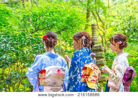 Kamakura, Japan - April 23, 2017: young women wearing japanese kimono in front of bamboo garden of Take-dera or Hokoku-ji Temple in Kamakura. Japanese culture and lifestyle. Spring season.