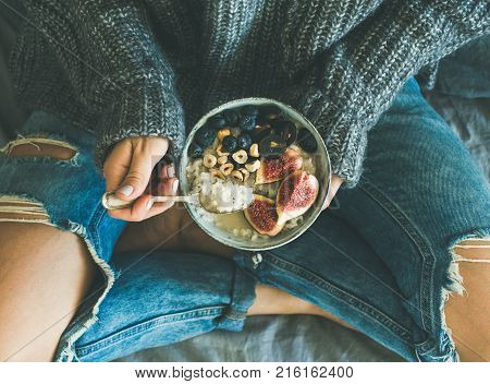 Healthy winter breakfast in bed. Woman in woolen sweater and shabby jeans eating rice coconut porridge with figs, berries, hazelnuts, top view. Clean eating, vegetarian, comfort food concept
