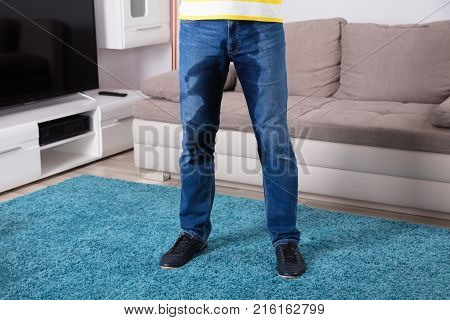Low Section View Of Person's Wet Jeans Standing On Carpet