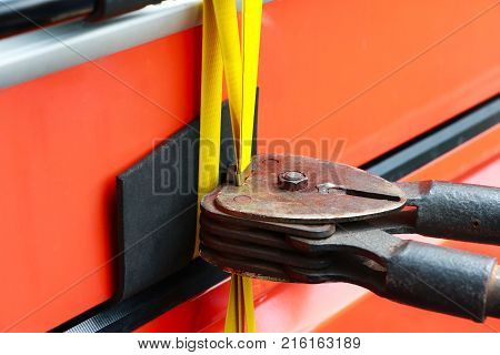 Asian Man Sealing Steel Strapping With The Sealless Combination Tool Or Poly Strapping Tools. Hand W