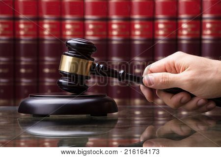 Close-up Of A Person's Hand Striking Gavel On Sounding Block In Courtroom