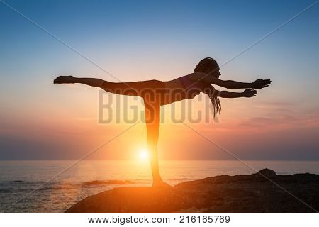 Silhouette of young woman doing gymnastics exercises on the seashore during sunset.