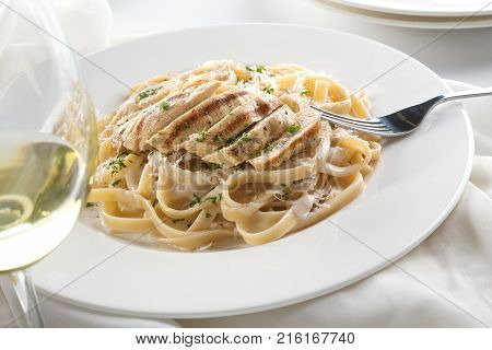 Delicious grilled chicken alfredo with fettuccine grated parmigiano reggiano and chopped parsley garnish.