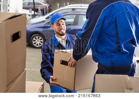 Close-up Of Two Happy Male Movers Holding Cardboard Box