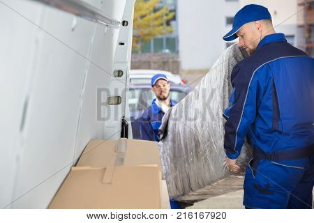 Two Happy Male Movers In Uniform Unloading Furniture From Truck