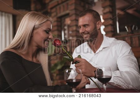 A young romantic couple on a romantic dinner at the restaurant drinks wine and enjoys in  love.