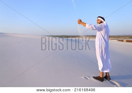 Young Arab guy who takes sand in hand and lifts it to smiling face and blows through fingers fine white grains of sand in bottomless desert on hot summer day. Swarthy, handsome Muslim with short dark hair dressed in kandura, long,