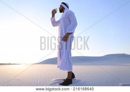 Stately Arab young man quenches thirst with glass of cool water and feels influx of strength and energy, smiles and looks to side, standing amidst endless sandy desert with pure white sand in open air on warm summer morning