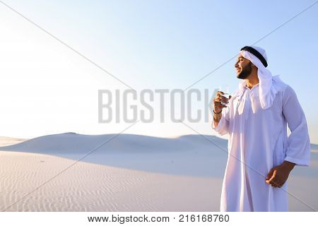 Stately Arab young man quenches thirst with glass of cool water and feels influx of strength and energy, smiles and looks to side, standing amidst endless sandy desert with pure white sand in open air on warm summer morning.