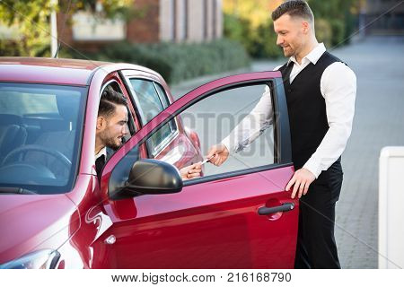 Valet Giving Receipt To Young Male Businessperson Sitting Inside Red Car
