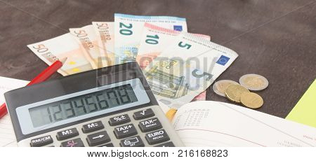 Banknotes and coins with calculator. Euro banknotes on wooden background. Photo for tax profit and costing. 50 euro 20 euro 10 euro. Money and finance