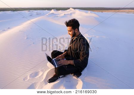 Young and handsome Muslim guy sits in social networks using computer, prints message or reads news, rests from turmoil of city, enjoys tranquility