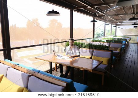 Lucky successful manager working with laptop and documents with diagrams at table indoors. Young gladden man enjoying good job and result, looking at cam and gesticulating yes. Concept of prosperous high class professionals and using modern devices for In