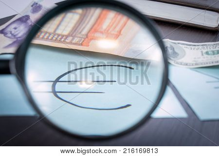 Word YES from finance signs. Banknotes and coins lying on notepad stickers with currency signs and Magnifier on wooden table. Accounting and taxes.