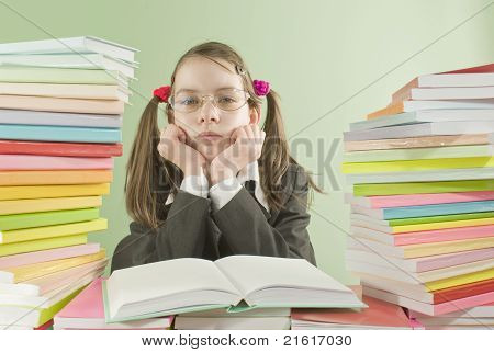 Bored School Girl Sitting At The Table With Stacks Of Books