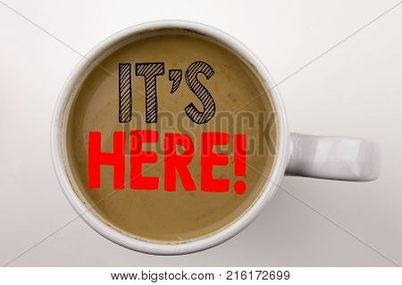 Word, Writing It's Here Text In Coffee In Cup. Business Concept For Advertisement On White Backgroun