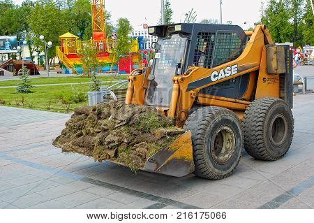 Tyumen, Russia - June 17. 2006: Tsvetnoy Bulvar city park. Skid loader working on gardening