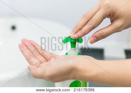 Female hands using wash hand sanitizer gel pump dispenser.