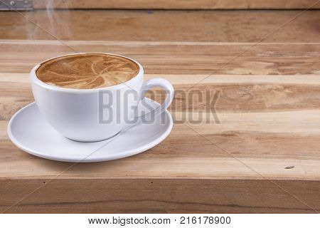 Cappuccino coffee and latte art on the wood table
