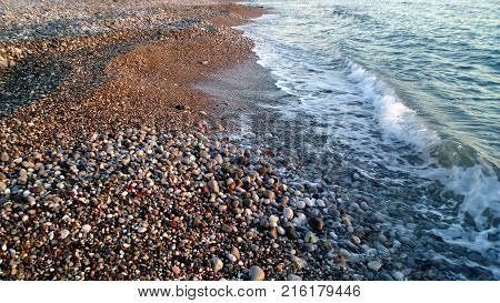 A small pebble on the shore of the sea and the beautiful runaway wave