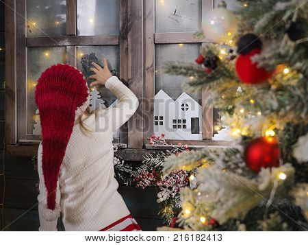Child in Christmas hat draws on a frozen window. Christmas tree beautiful decoration