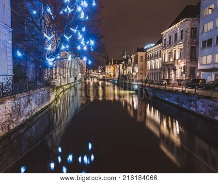 Ghent, Flanders, Belgium - January 3th, 2017. Christmas illuminated birds installation and medieval houses reflected in night canal by evening illumination in historical Gent city center by night.