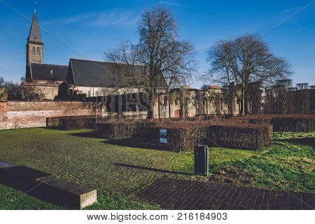 January, 3th, 2017 - Ghent, East Flanders, Belgium. Old medieval church and brick wall of Gent St Bavo abbey also known as Sint-Baafsabdij by sunny day.
