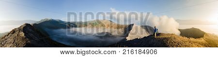 Panorama of Gunung Bromo inner volcano crater with sulphur fumes and morning mist with male adult gazing at sunrise. Java Indonesia.