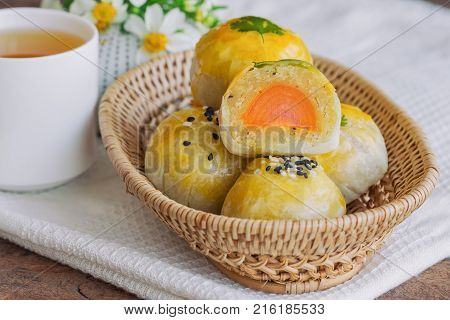 Delicious Chinese pastry or moon cake filled with mung bean paste and salted egg yolk on wood basket. Homemade Chinese pastry served with tea on wood table in side view close up with copy space. Homemade bakery concept of moon cake or Chinese pastry.