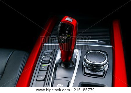 Red Automatic gear stick (transmission) of a modern car multimedia and navigation control buttons. Car interior details. Transmission shift.